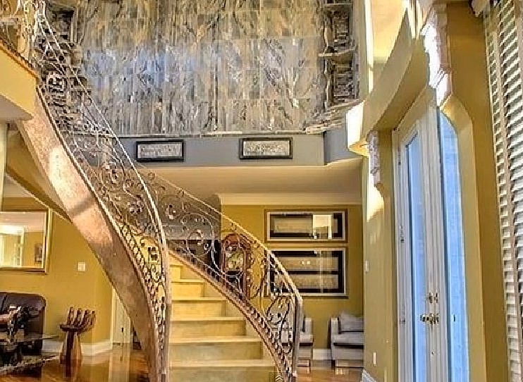 Elegant spiral staircase with a water fall marble wall in the background. Grow op mansion, King City Grow Op Mansion in Ontario, mansion, grow op, marijuana, 420, illegal, drug dealers, drugs, abandoned mansion, abandoned Ontario, king city grow op, keene